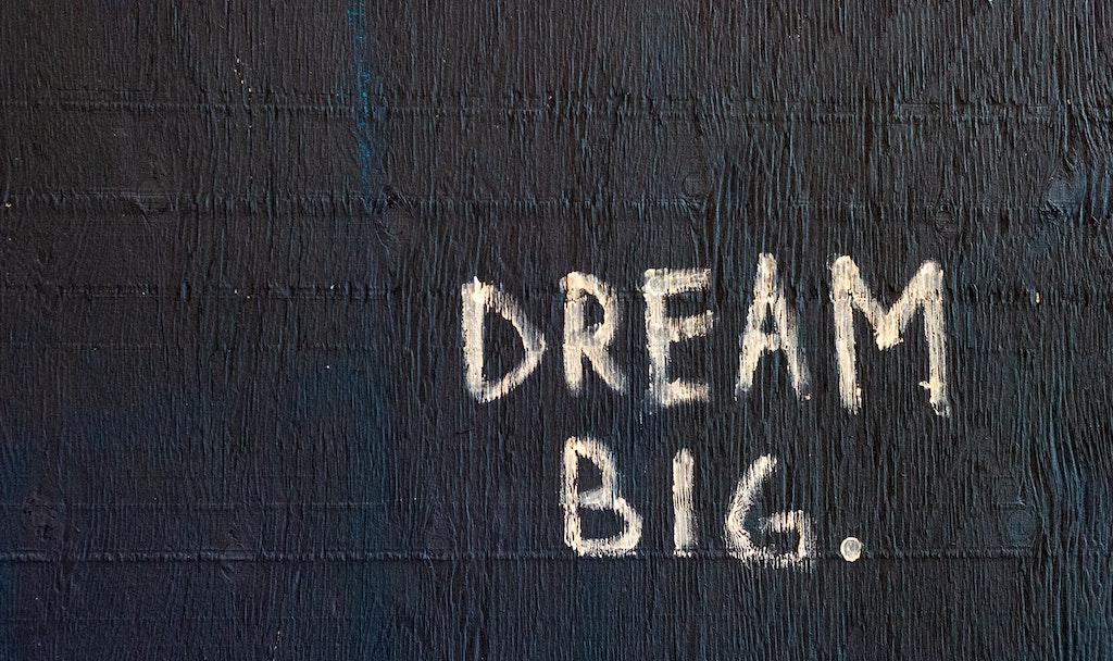 """""""Dream Big"""" als Tag auf eine Wand gesprüht. Eines von vielen Statements, das suggeriert, wir müssten uns auch in Hinblick auf unseren Traumjob immer weiter optimieren."""