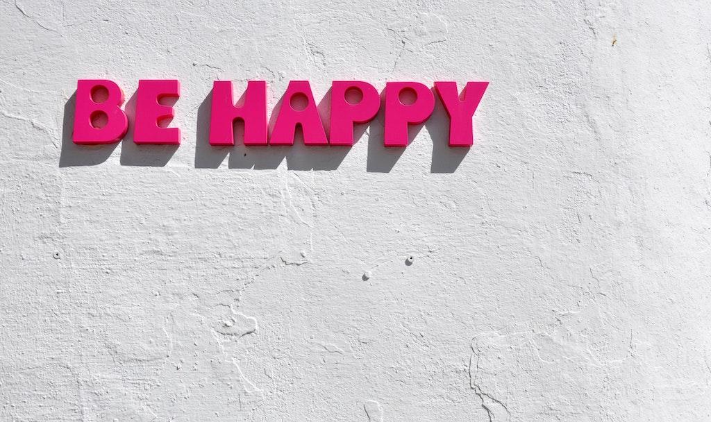 """Schriftzug """"Be Happy"""" an der Wand - zwanghafte Positivität ist anstrengend."""